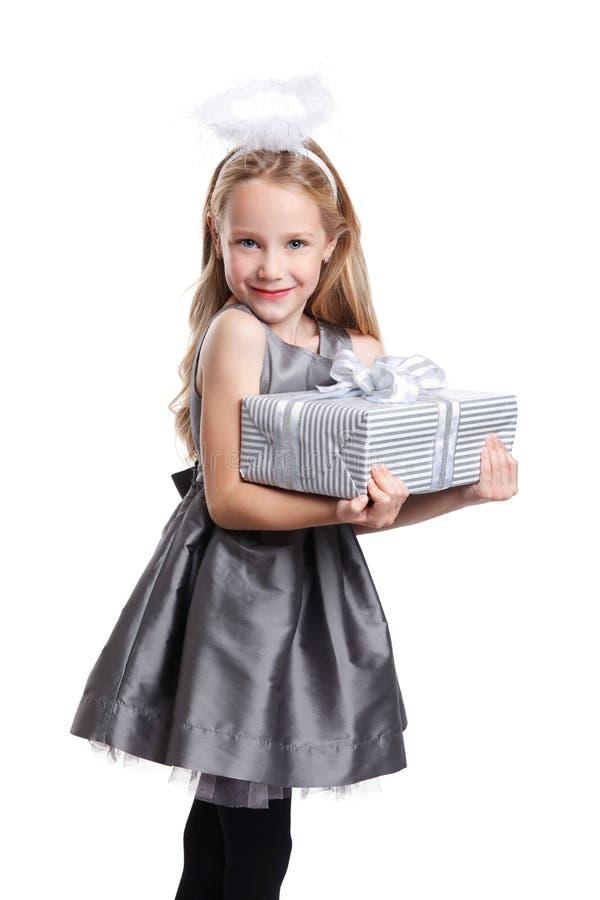 Bella bambina che tiene un regalo avvolto immagine stock libera da diritti