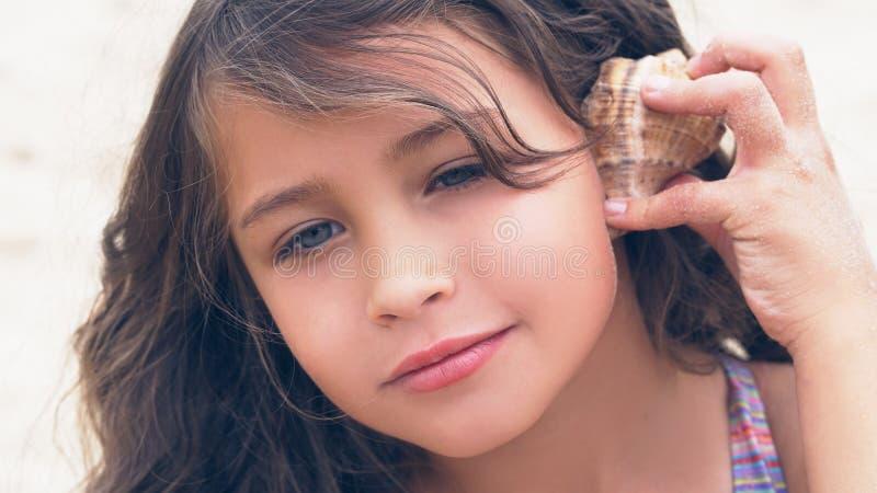 Bella bambina con capelli ricci lunghi che ascolta la musica del mare in conchiglia sulla spiaggia fotografia stock