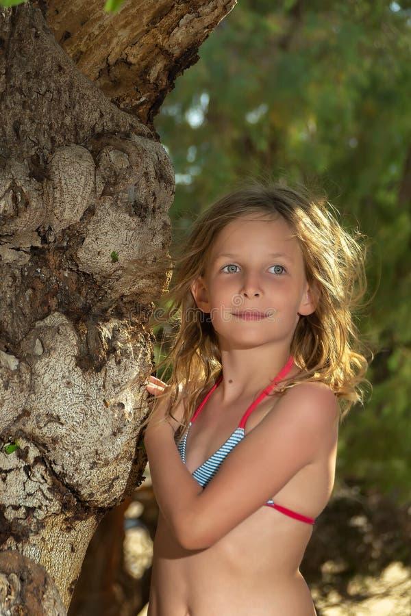 Bella bambina con gli occhi grigi con una condizione piacevole di sorriso al vecchio albero nel tramonto immagini stock