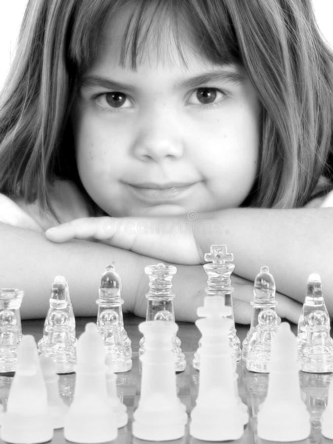 Bella bambina con la scheda di scacchi di vetro immagini stock