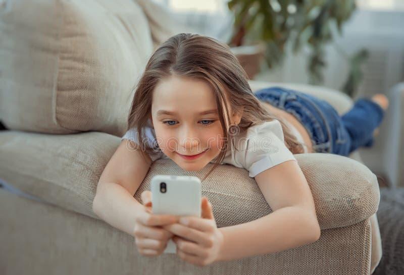 Bella bambina con lo smartphone Svago, bambini, tecnologia e concetto della gente fotografie stock libere da diritti