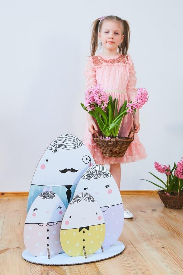 Bella bambina di Pasqua 2019 in un vestito con le decorazioni di Pasqua Grandi uova di Pasqua e coniglietti, posto variopinto Mol immagine stock