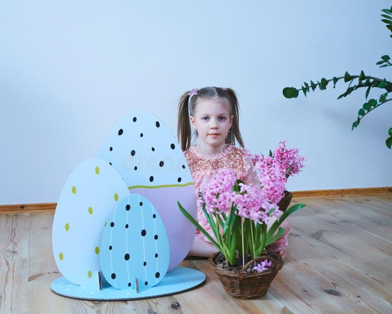 Bella bambina di Pasqua 2019 in un vestito con le decorazioni di Pasqua Grandi uova di Pasqua e coniglietti, posto variopinto Mol fotografia stock libera da diritti