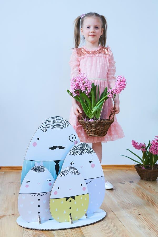 Bella bambina di Pasqua 2019 in un vestito con le decorazioni di Pasqua Grandi uova di Pasqua e coniglietti, posto variopinto Mol fotografia stock