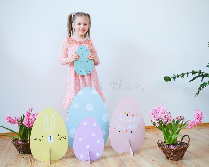 Bella bambina di Pasqua 2019 in un vestito con le decorazioni di Pasqua Grandi uova di Pasqua e coniglietti, posto variopinto Mol immagini stock