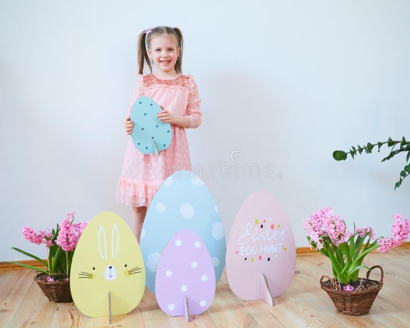 Bella bambina di Pasqua 2019 in un vestito con le decorazioni di Pasqua Grandi uova di Pasqua e coniglietti, posto variopinto Mol immagini stock libere da diritti