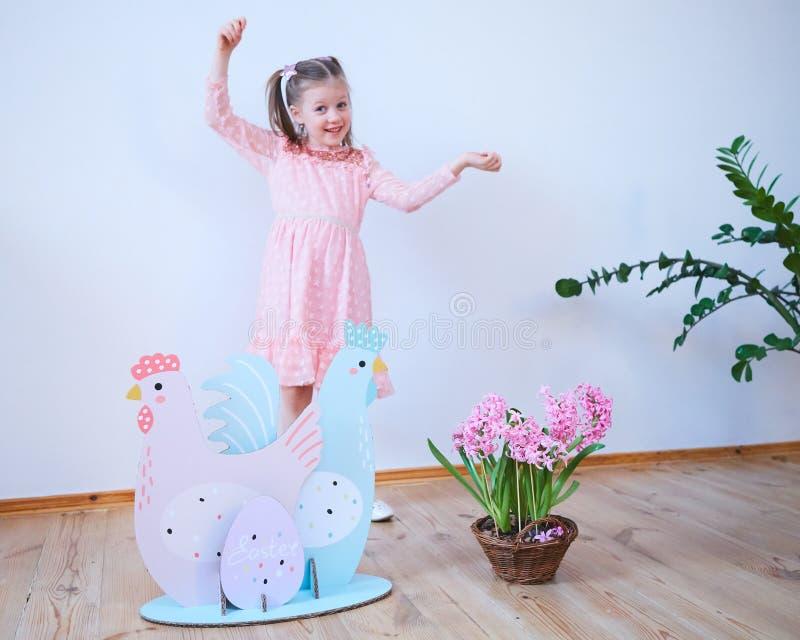 Bella bambina di Pasqua 2019 in un vestito con le decorazioni di Pasqua Grandi uova di Pasqua e coniglietti, posto variopinto Mol fotografie stock libere da diritti