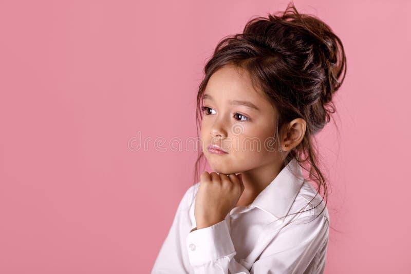 Bella bambina dubbiosa e premurosa in camicia bianca con l'acconciatura fotografie stock