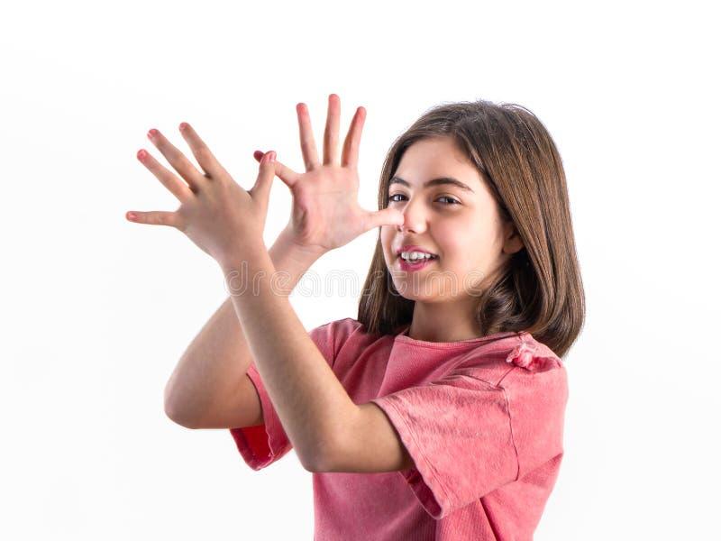 Bella bambina felice che posa davanti alla macchina fotografica sulla b bianca fotografie stock libere da diritti