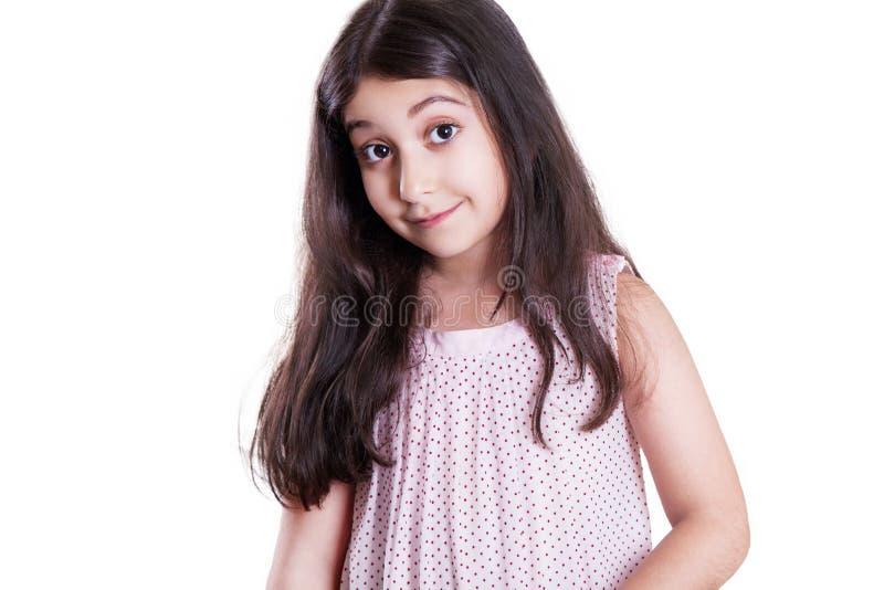 Bella bambina felice con capelli scuri lunghi ed il vestito che esaminano macchina fotografica fotografia stock