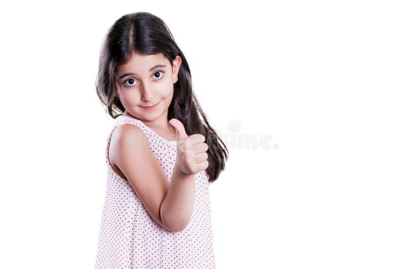 Bella bambina felice con capelli scuri lunghi ed il vestito che esaminano macchina fotografica con i pollici su fotografie stock libere da diritti