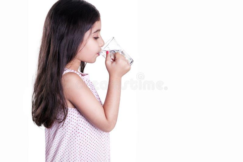 Bella bambina felice con capelli scuri lunghi ed il vestito che tengono bicchiere d'acqua immagine stock libera da diritti