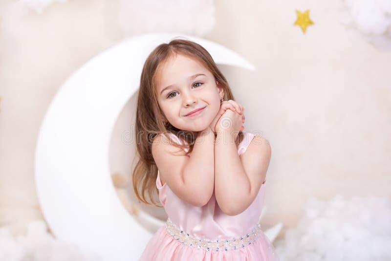 Bella bambina nello studio su un fondo della luna, delle stelle e delle nuvole La bambina sta sognando Sogni dolci cute fotografia stock