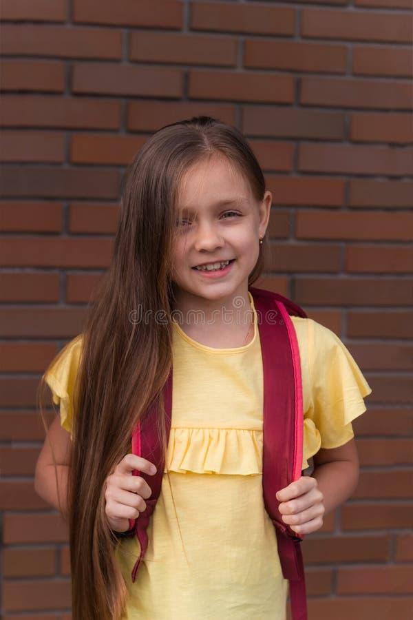 bella bambina sorridente con uno zaino sui precedenti di un muro di mattoni immagini stock libere da diritti