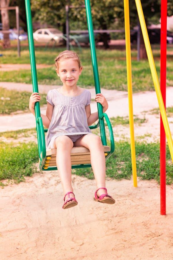Bella bambina sull'oscillazioni all'aperto nel campo da giuoco immagini stock