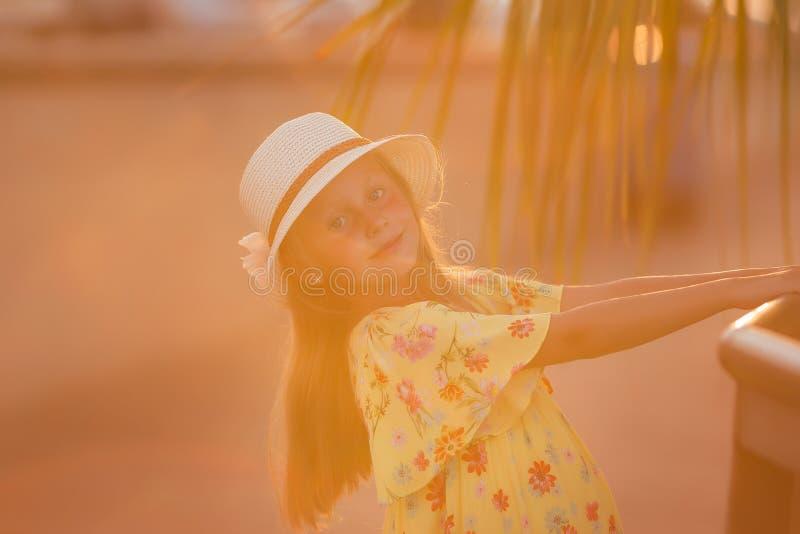Bella bambina sveglia al mare su un fondo di tramonto Ritratto di una ragazza in un cappello di paglia fotografia stock libera da diritti