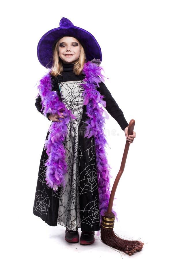Bella bambina sveglia nella tenuta del costume di Halloween della strega la scopa immagine stock libera da diritti