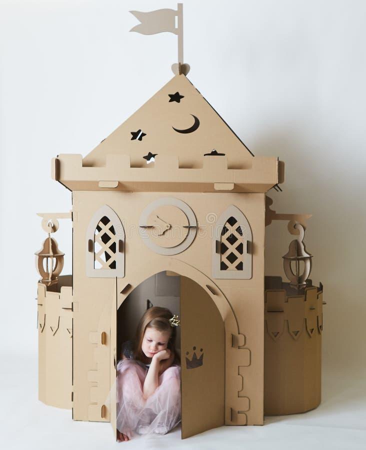 Bella bambina triste in vestito da principessa che gioca con il suo castello del giocattolo immagine stock