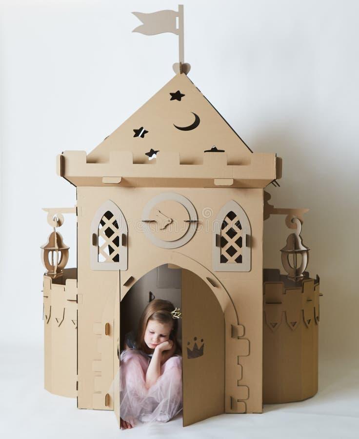 Bella bambina triste in vestito da principessa che gioca con il suo castello del giocattolo fotografia stock