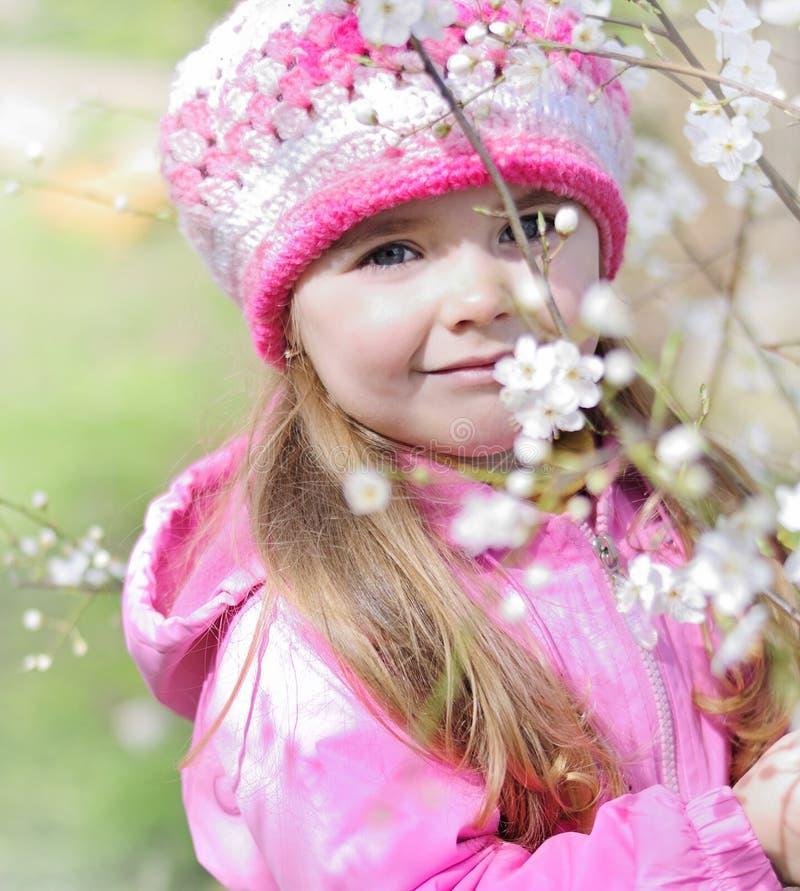 Bella bambina vicino ad un albero di fioritura fotografia stock libera da diritti