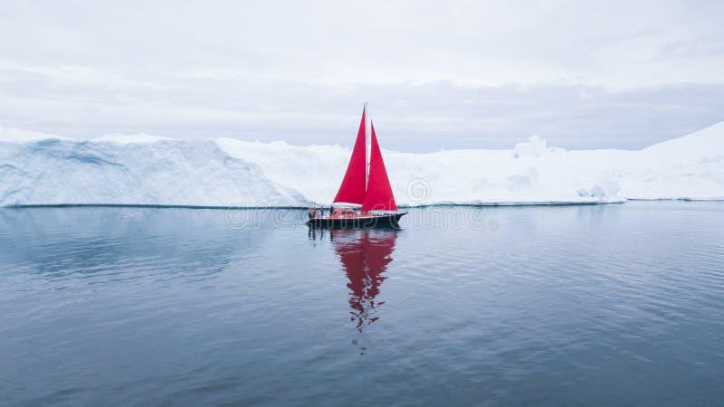 Bella barca a vela rossa accanto ad un iceberg massiccio fotografia stock libera da diritti