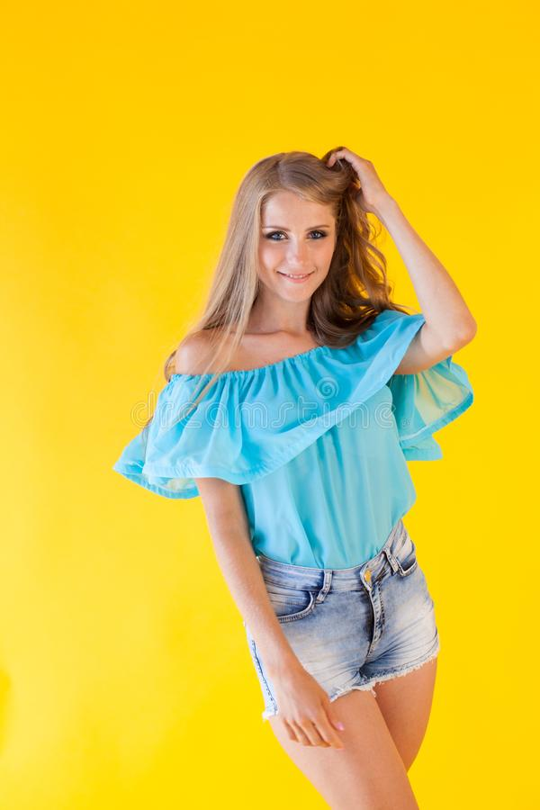 Bella bionda con gli shorts blu su un fondo giallo immagine stock libera da diritti