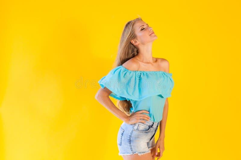 Bella bionda con gli shorts blu su un fondo giallo immagine stock