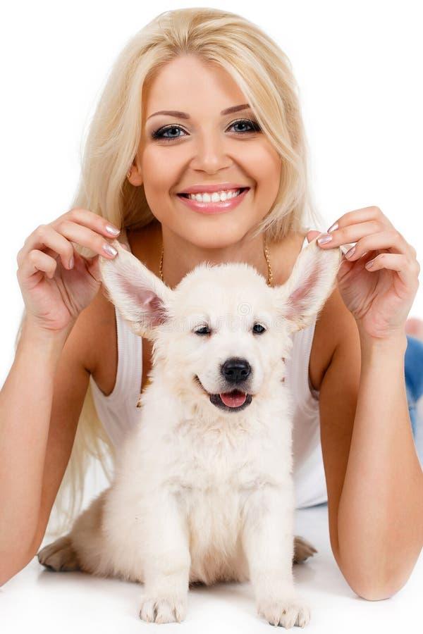 Bella bionda con un piccolo cucciolo bianco di Labrador immagini stock libere da diritti