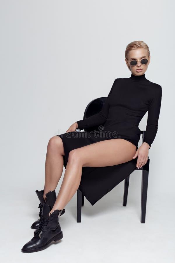 Bella bionda con un vestito elegante e nero con occhiali da sole su una sedia nera in studio su fondo bianco fotografie stock
