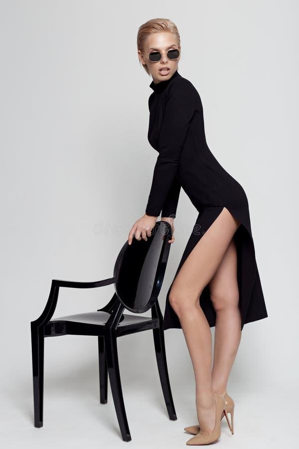 Bella bionda con un vestito elegante e nero con occhiali da sole su una sedia nera in studio su fondo bianco immagini stock libere da diritti