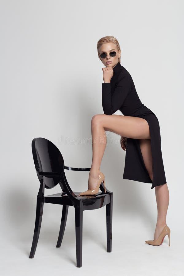 Bella bionda con un vestito elegante e nero con occhiali da sole su una sedia nera in studio su fondo bianco fotografia stock