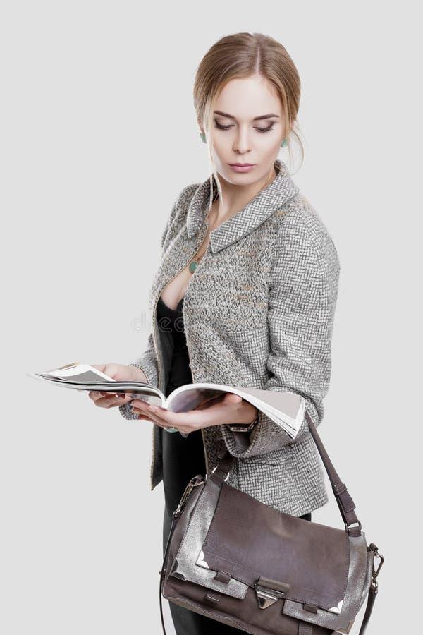 bella bionda della donna di affari in vestito nero, rivestimento leggente una rivista sul fondo grigio immagine stock libera da diritti