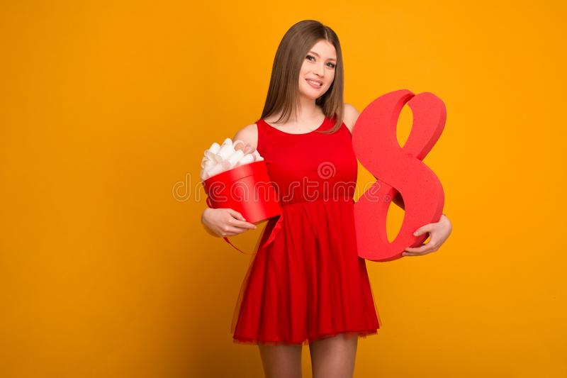 Bella bionda in un vestito rosso con un regalo e numero otto in mani immagine stock libera da diritti