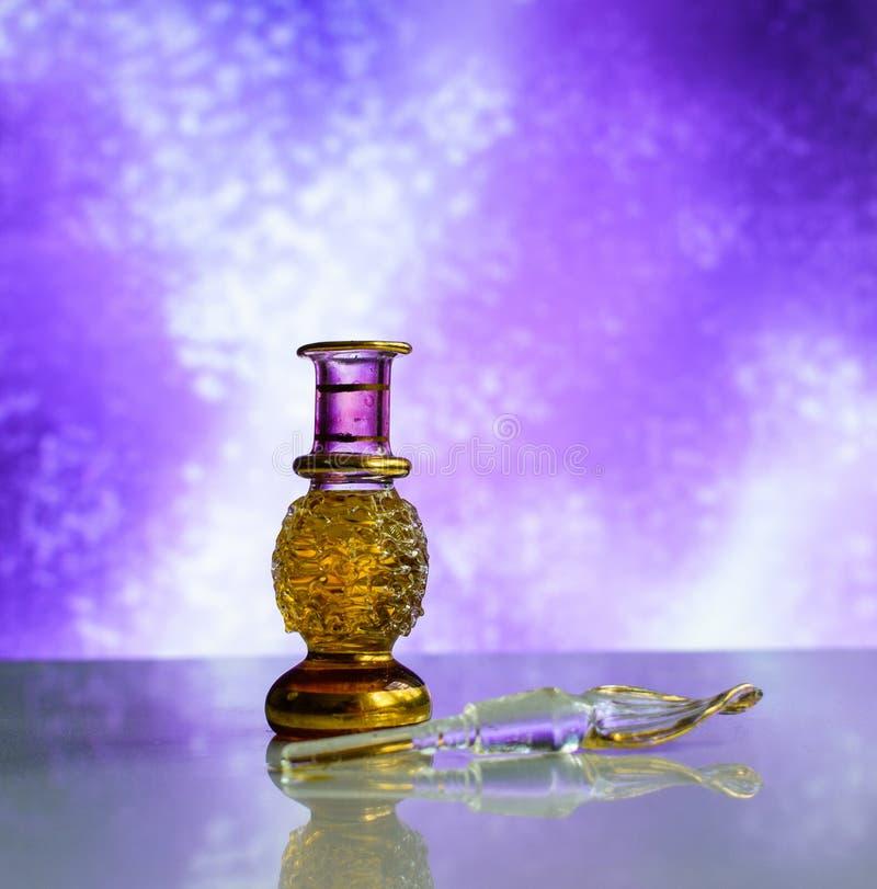 Bella bottiglia cosmetica di vetro di profumo su un fondo affascinante lilla immagine stock