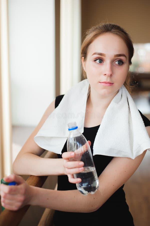Bella bottiglia di acqua della tenuta di resto della presa della donna dopo la pedana mobile funzionata concetto di sport di salu immagini stock