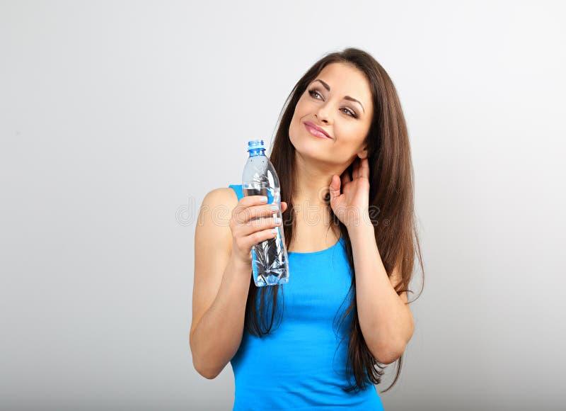 Bella bottiglia esile sportiva felice della tenuta della donna con acqua e con il pensiero come perdere peso su fondo blu immagine stock libera da diritti