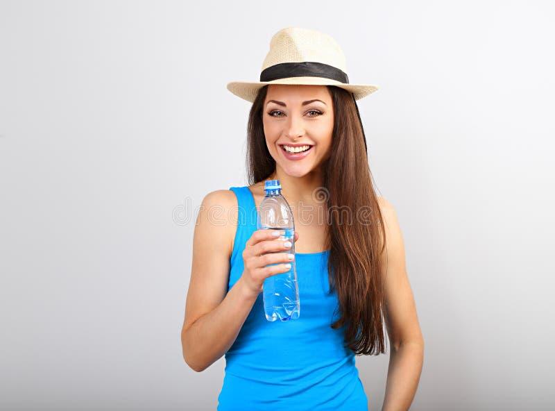 Bella bottiglia esile sportiva felice della tenuta della donna con acqua su fondo blu immagine stock libera da diritti