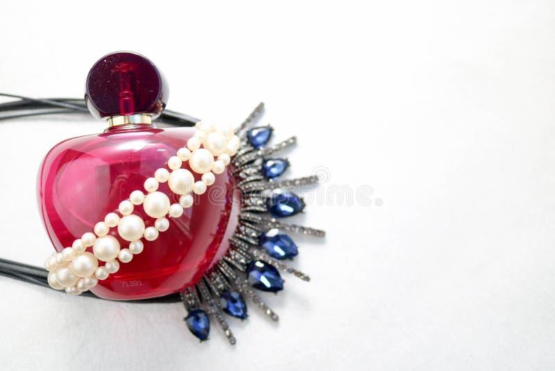 Bella bottiglia trasparente di vetro rosa di profumo femminile decorata con le perle grige bianche ed i diamanti blu e del posto  fotografie stock
