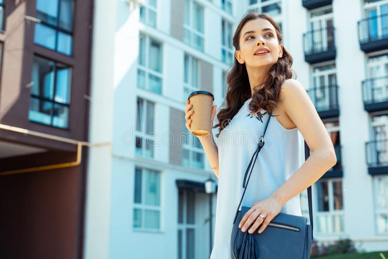 Bella bruna che fora caffè asportabile in sua mano immagini stock