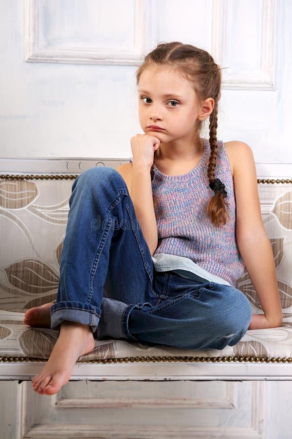 Bella calma che pensa la ragazza infelice del bambino che si siede sul banco dentro immagini stock libere da diritti
