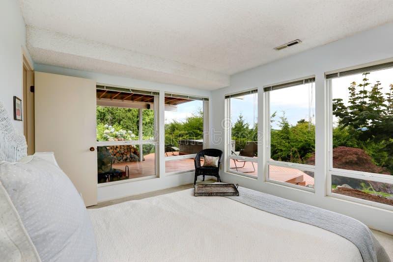 Bella camera da letto bianca con la parete di vetro immagini stock