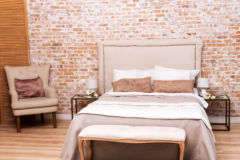Bella camera da letto del sottotetto con il letto e poltrona vicino al muro di mattoni - Letto ribaltabile a muro ...