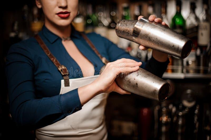 Bella cameriera al banco sexy che fa cocktail in agitatore immagini stock