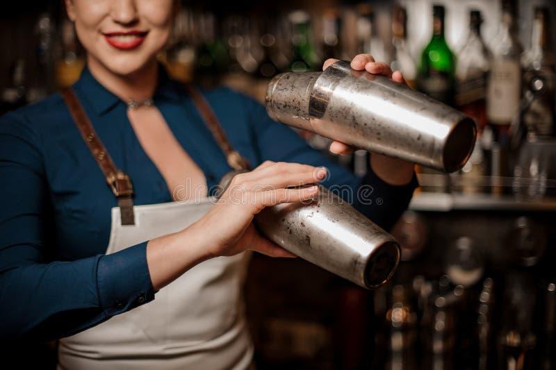 Bella cameriera al banco sexy sorridente che fa cocktail in un agitatore fotografia stock