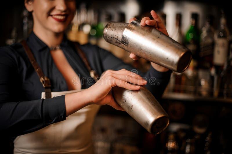 Bella cameriera al banco sorridente che fa cocktail in agitatore fotografia stock libera da diritti