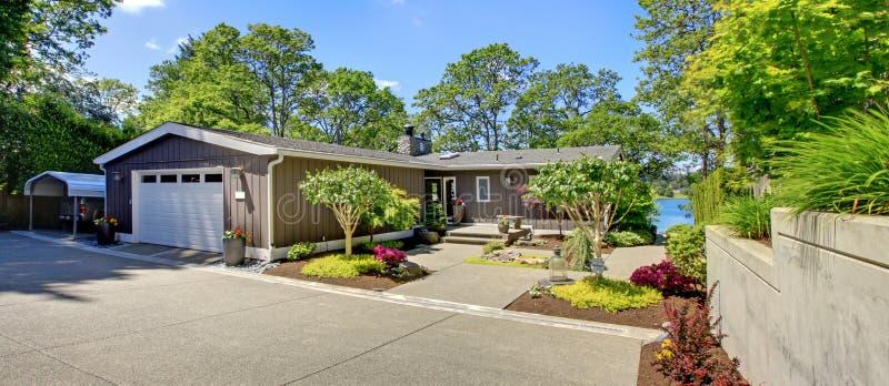 Bella casa con il garage, la vista del lago e la grande iarda di fronte. immagini stock libere da diritti