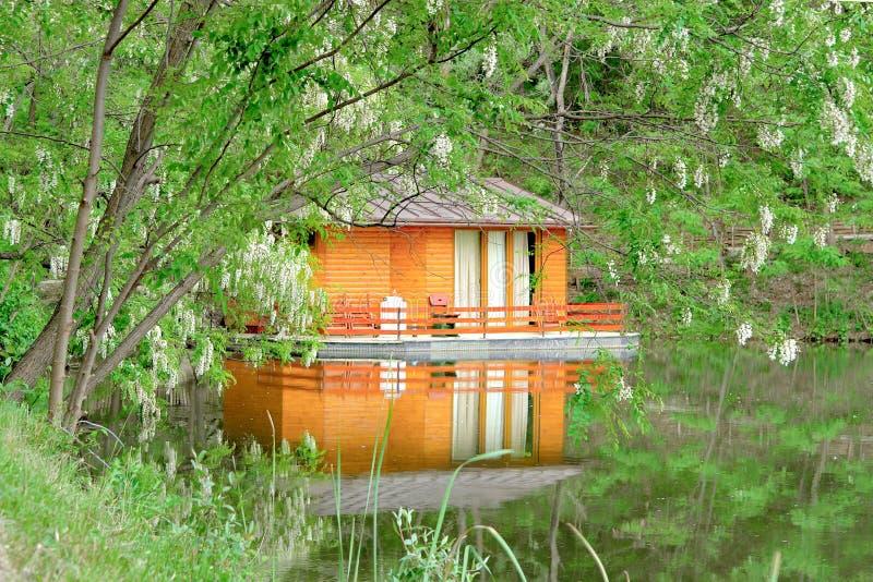 Bella casa di legno arancio sulla foresta del lago fotografia stock