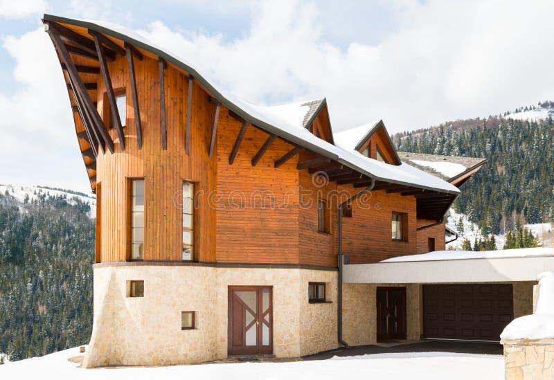 Bella casa di legno moderna coperta in neve, stazione sciistica Donovaly fotografia stock libera da diritti