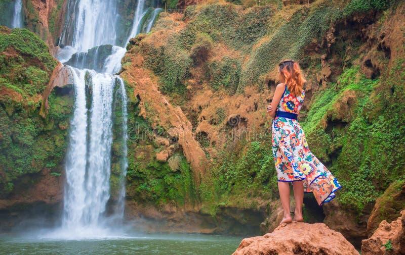 Bella cascata nel Marocco Indietro della donna in bello vestito che guarda caduta Ouzoud Natura esotica del Nord Africa, fotografia stock libera da diritti