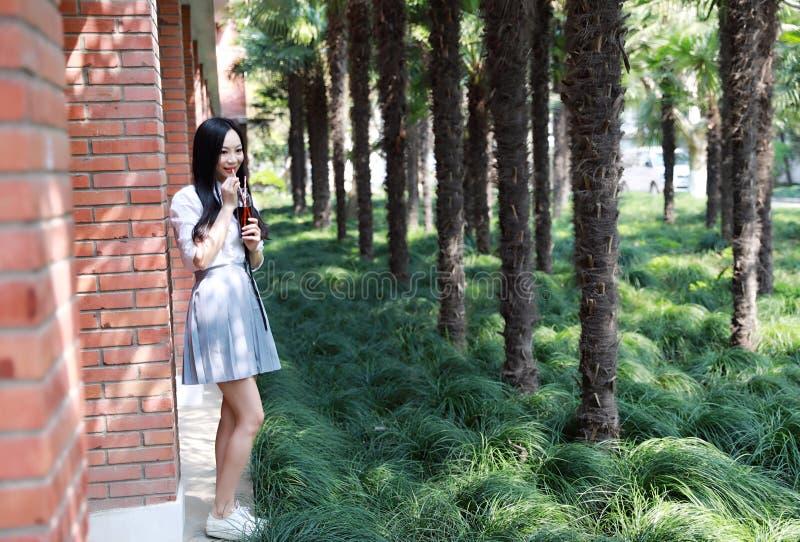 Bella cola adorabile sveglia felice della bevanda dello studente di college della High School della ragazza al portico dell'aula fotografia stock libera da diritti